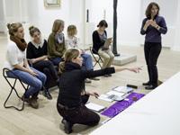 Im Museum erklärt die Workshopleiterin der sitzenden Gruppe ein Werk. Daneben steht die Gebärdensprachdolmetscherin. Auf dem Boden liegen die Malsachen.