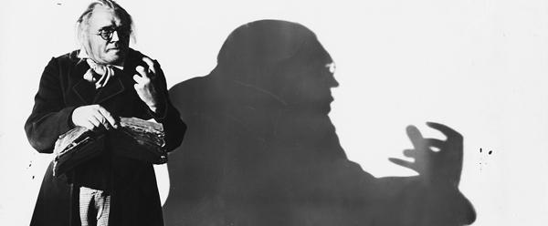 schwarzweiß-Fotografie: links ist der Doktor in Vorderansicht, auf der Wand hinter ihm ganz langezogen und gespenstisch sein Schatten mit der gekrallten Hand.