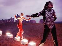 Michael Jackson läuft auf von innen heraus leuchtende weiße Kästchen und singt dabei. Im Hintergrund Skyline einer Stadt und eine Tänzerin in rotem Kleid.