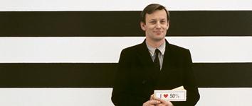 """Wandarbeit: horizontale ca. handbreite Streifen von Schwarz und Weiß. Kippenberger steht im schwarzen Anzug davor und hält einen Schein """"I love 50%"""". Das Love ist ein rotes Herz."""
