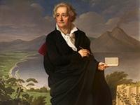 Wanderer Goethe mit Buch und Stift vor einer Landschaft mit Gebirge, See und Stadt