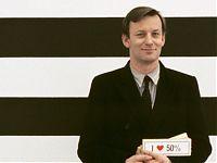 Hintergrund breite horizontale Schwarz-Weiß-Streifen, davor der Künstler im schwarzen Anzug