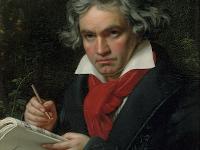 Beethoven mit grauen Naturlocken und in feiner Kleidung schwarzer Anzug, roter Schal und weißes Hemd, hält ein dickes Notenheft und eine Feder, um darin zu schreiben.