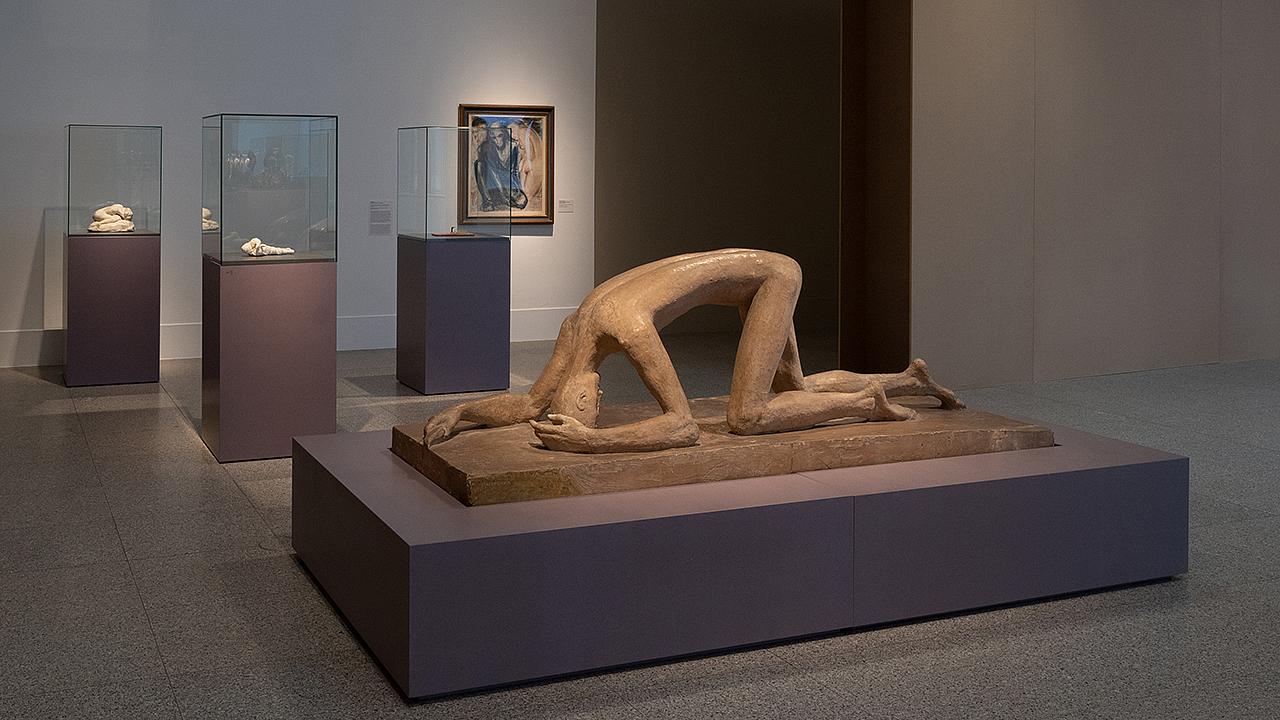 """Skulptur leicht bräunlich, Mensch knieend und stützt Arme auch auf Boden ab mit Unterarm - der Mensch scheint sich bei dieser Art Fortbewegung """"auszuruhen"""", da der Scheitel des Kopfes ebenfalls den Boden berührt."""