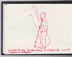 Bauarbeiter steht mit der Schaufel in der Hand und wartet auf seinen Einsatz. Hinter ihm ist der Bagger am Werk und hebt etwas aus.